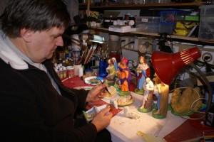 Šmarski župnik Janez Gerčar med izdelovanjem (barvanjem) jaslic. Jaslice je rad poklanjal različnim ljudem, večim je posodil in končno Šmarčanu Simonu tudi poklonil modele za izdelovanje jaslic.